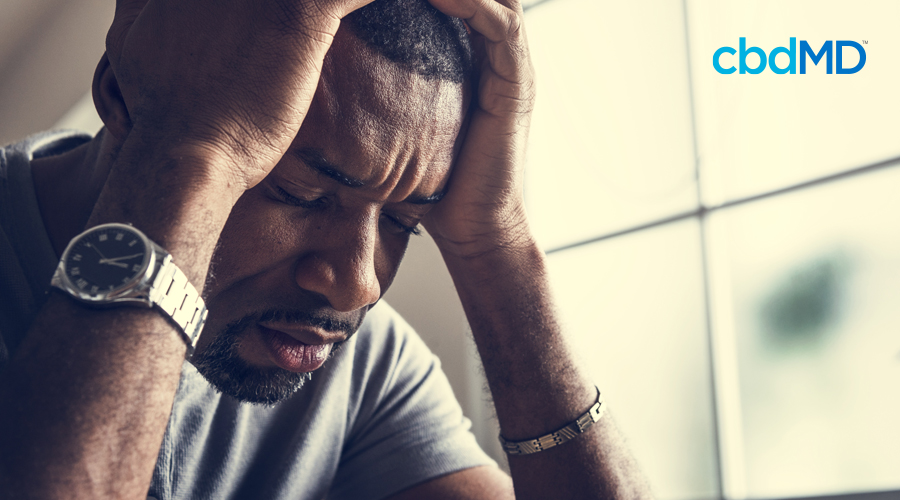 Man sitting with his hands on the sides of his head that is stressed out