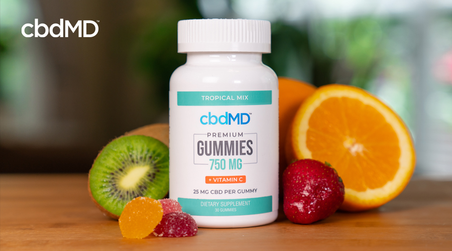 A bottle of 750 mg cbdMD CBD Gummies sits on a wooden table among assorted fruit