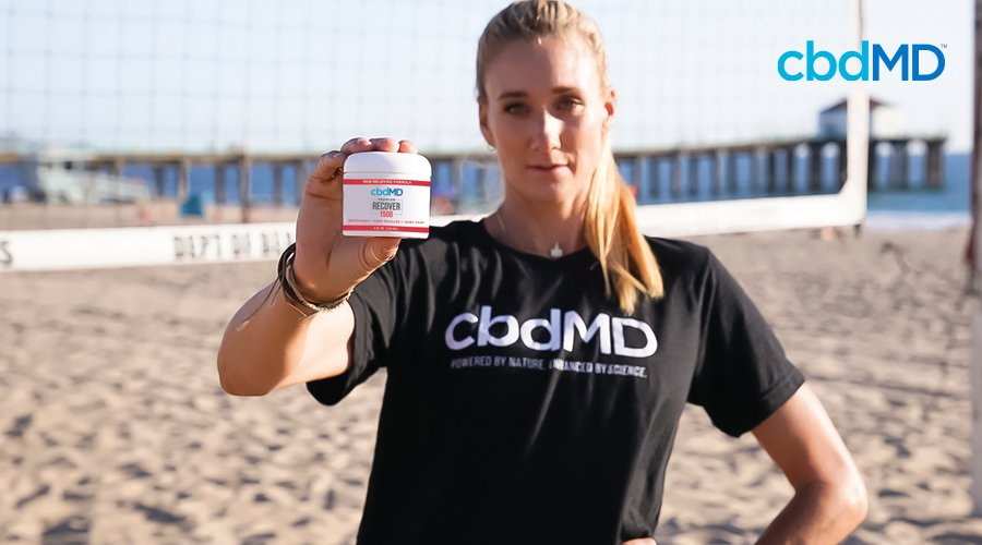 Kerri Walsh Jennings stands on beach in front of volleyball net holding cbdMD CBD Recover 1500 mg tub