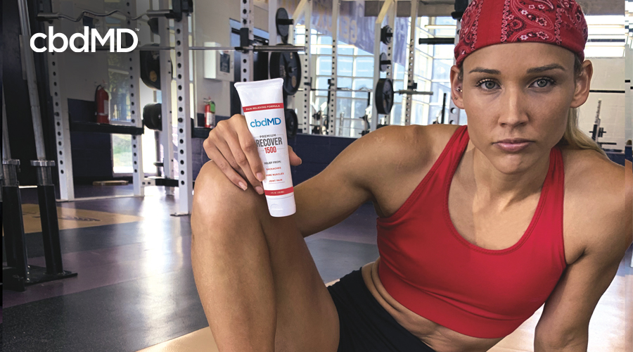 athlete and entertainer Lolo Jones poses in red bandana and red shirt at weight room with cbdMD Recover topical 1500 mg squeeze tube