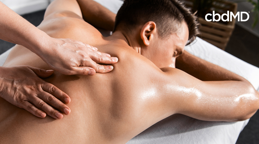 Dark-haired man lays on stomach on a white towel as pair of hands rub along back
