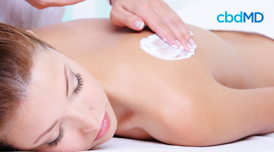 Light-haired woman rests while manicured hand rubs skincare cream on her left shoulder