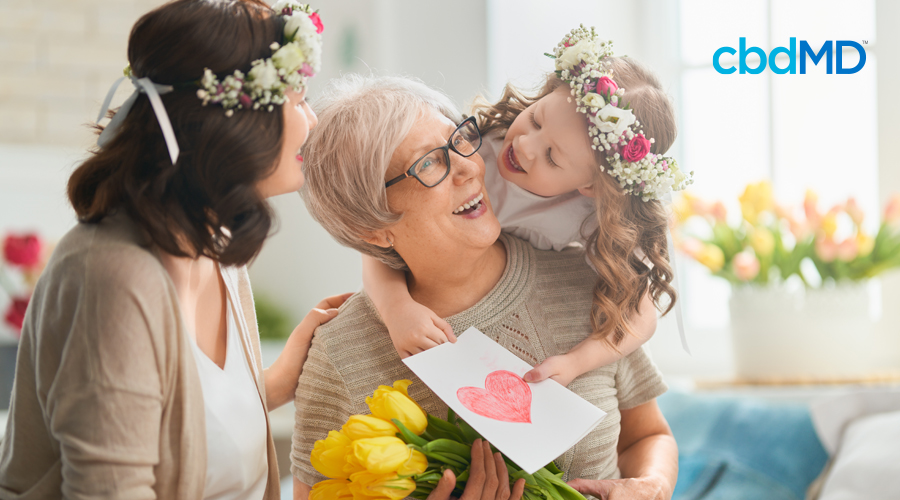 Young child with long blonde hair and flower headband sits on grandmas shoulders holding yellow flowers and hands her card with drawn heart on cover as dark-haired mom with flower headband places hand on shoulder