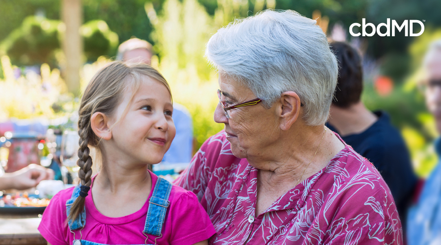 Light-haired granddaughter with braids and pink shirt with overalls smiles and sits outside at picnic table with gray short-haired grandmother in glasses and pink floral blouse
