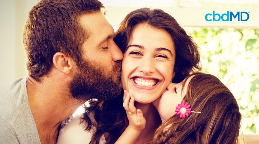 Dark-haired woman smiles as husband with short brown hair and beard kisses cheek and young daughter with flower in brown hair kisses other cheek