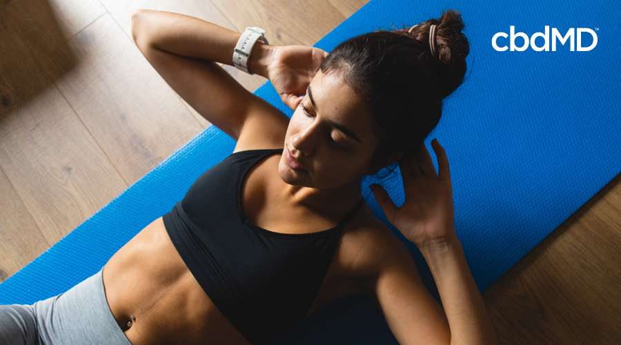 Dark-haired woman in back workout shirt and gray pants doing crunches on blue yoga mat