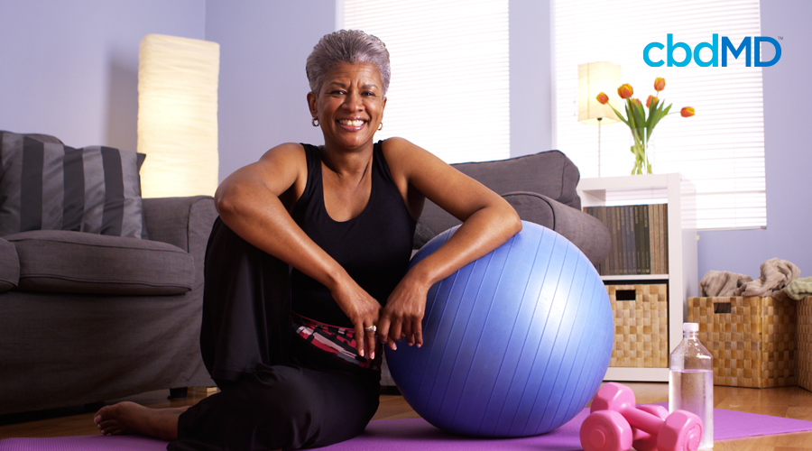 Gray-haired lady sits in living room on pink yoga mat in black workout attire next to blue exercise ball and pink weights and water bottle