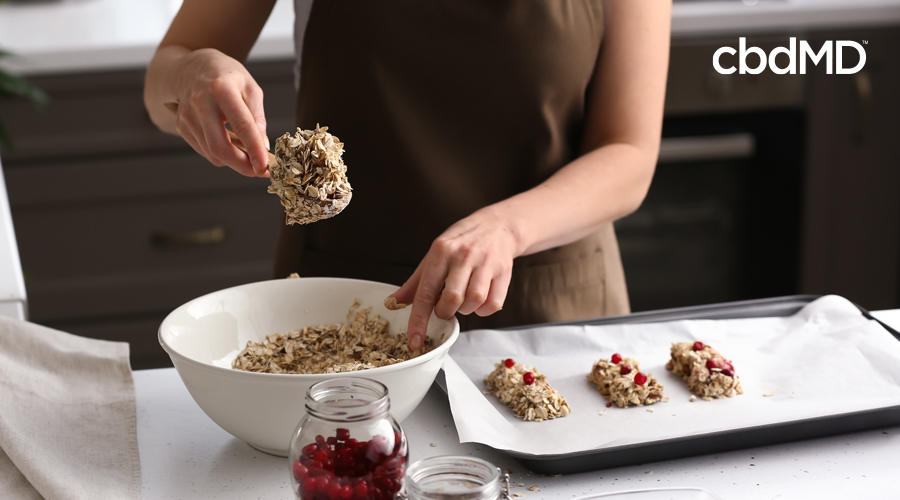 Woman in brown apron scoops protein balls of oats and berries out of mixing bowl onto baking sheet with parchment paper