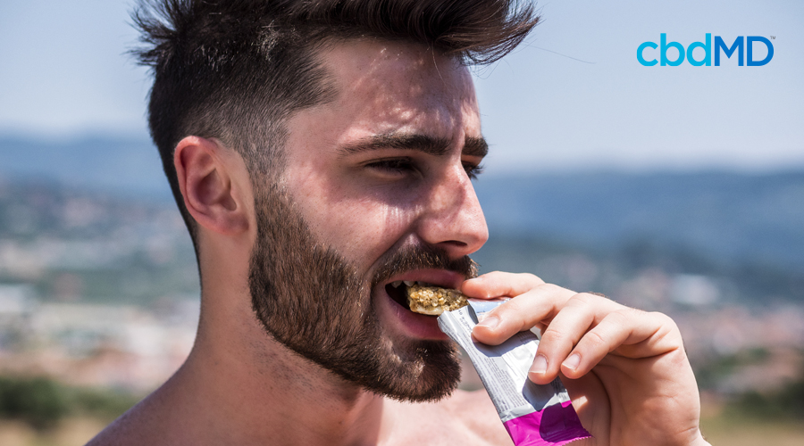 Shirtless dark-haired man with short hair and beard eats protein bar while standing outside