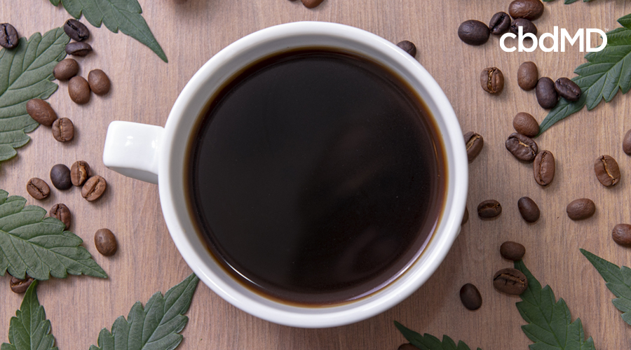 Coffee cup with leaves and beans around it
