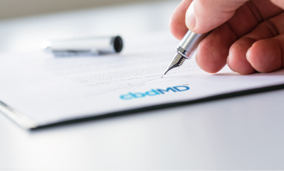 Picture Of A Hand Writing On A cbdMD Paper